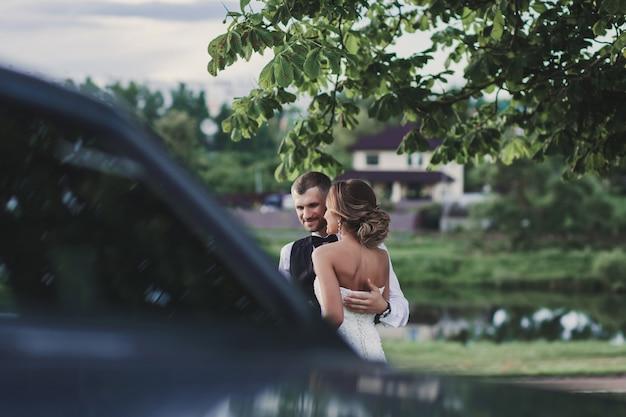 Bride and groom near retro car