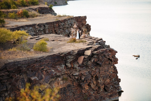 Bride and groom near the wedding decoration at a ceremony on a cliff of rock near the water at sunset