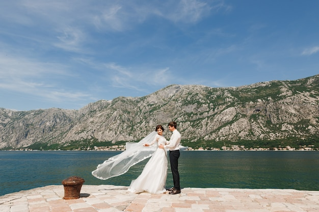 Bride and groom on the pier in the bay of kotor