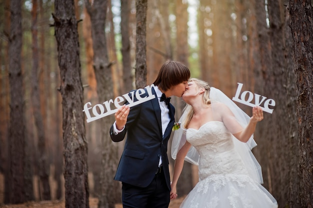 Bride and groom in a pine forest in autumn