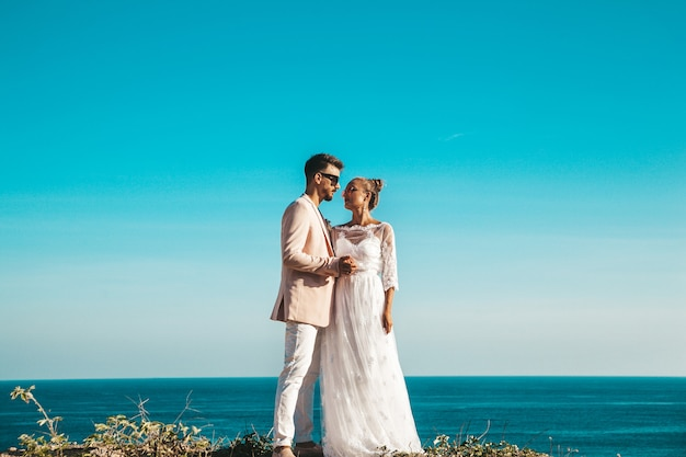 Bride and groom posing on the cliff behind blue sky and sea