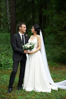 Bride and groom posing in a forest