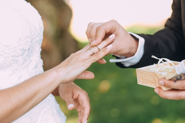 Bride groom putting golden rings to finger of each other