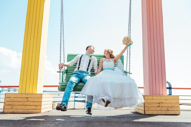 The bride and groom ride on a swing
