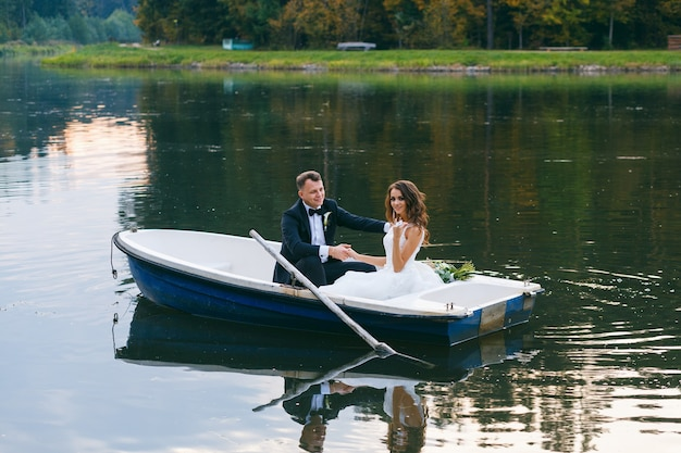 The bride and groom in a rowboat on the lake at sunset
