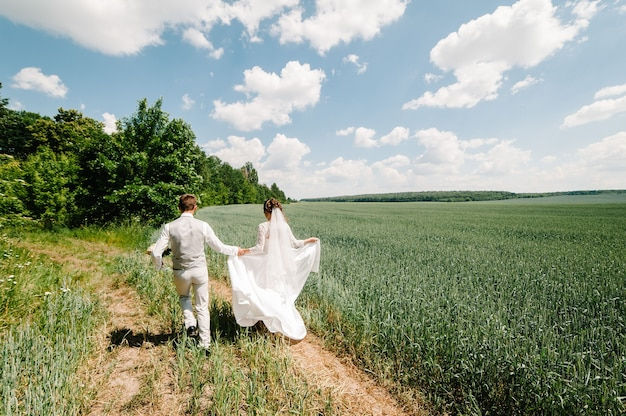 The bride and groom run in the field after wedding ceremony.