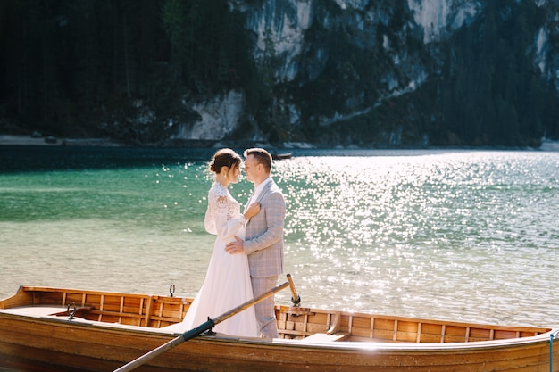 Bride and groom sailing in wooden boat, with oars at lago di braies lake in italy