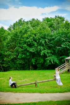 Bride, groom and seesaw