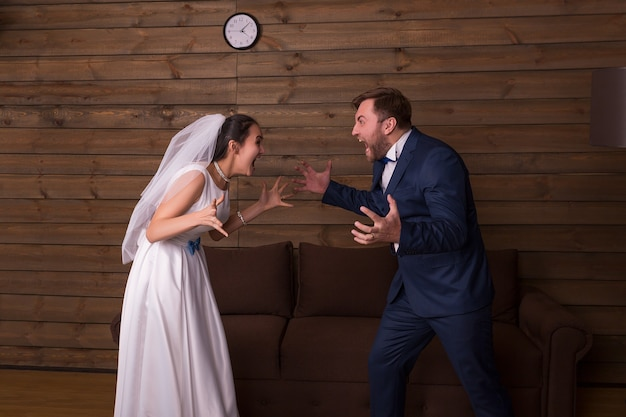 Bride and groom shouting at each other. newlyweds complex relationship