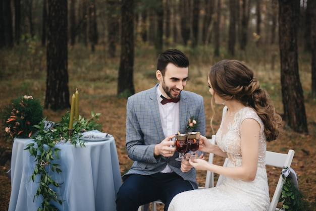 The bride and groom sit at a table set for two in the woods