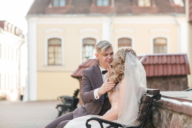 Bride and groom sitting on a bench on a city street. holidays and events