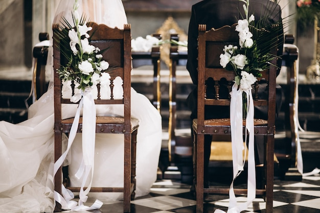Bride and groom sitting on chairs on their wedding day, from the back