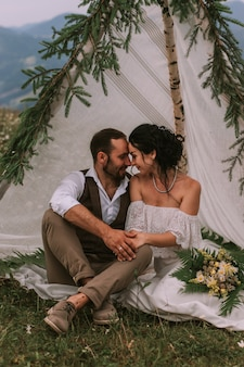 Bride and groom sitting in a wedding hut
