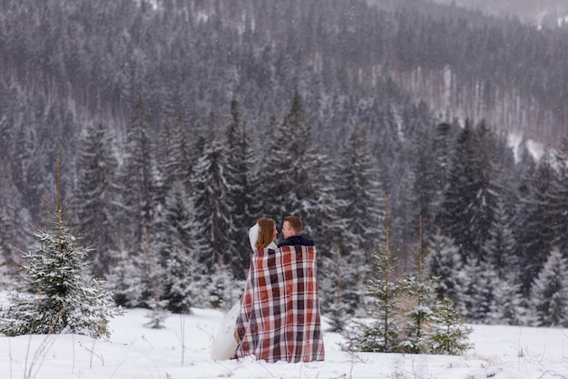 The bride and groom stand against the backdrop of the mountains and cuddle under a rug to keep warm. winter wedding