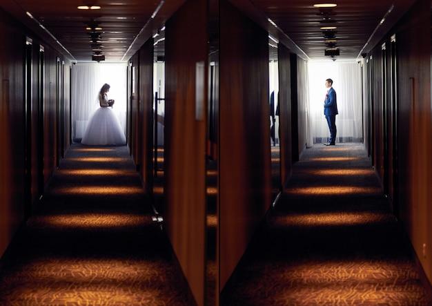 Bride and groom stand in the dark corridor