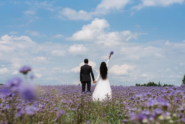 Bride and groom stand in a field of flowers in the summer on the wedding day