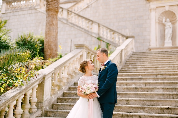 The bride and groom stand hugging on the stairs of the nativity of the blessed virgin mary church