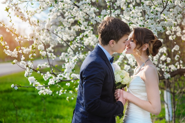 Bride and groom stand near a flowering tree in the spring garden