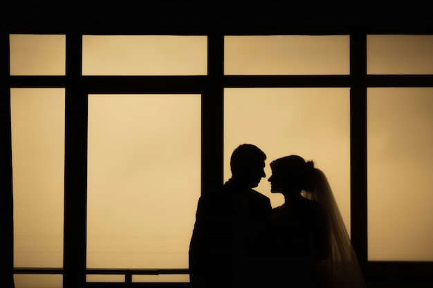 Bride and groom stand near the window.