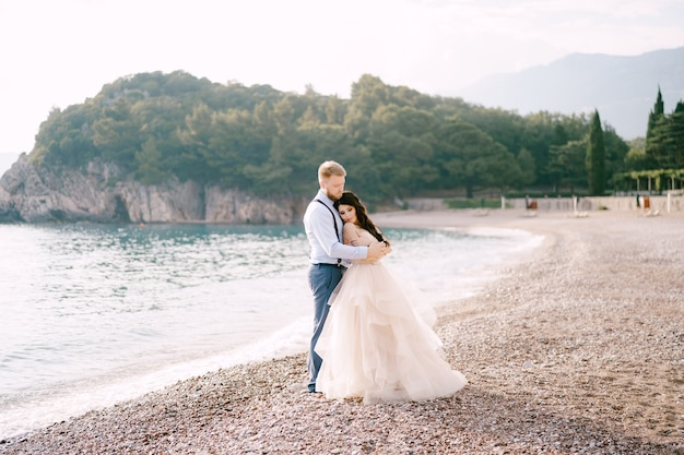 The bride and groom stand on the pebbled seashore and hug the groom hugs the brides shoulders