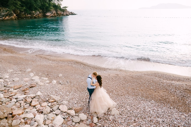 The bride and groom stand on the pebbled seashore and hug
