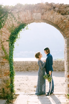 The bride and groom stand side by side in an old arch, the bride put her hands on the groom's chest. high quality photo