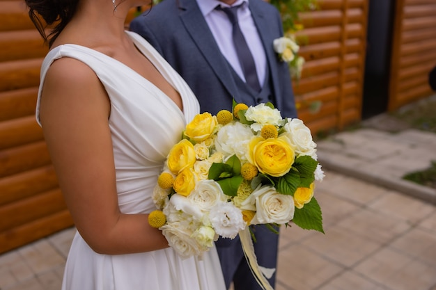 Bride and groom standing on green grass and holding a bouquet of white and yellow flowers with green