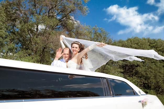 Bride and groom standing in limo waving