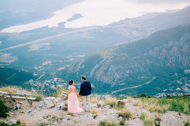 Bride and groom standing on the mountain against the backdrop of the bay of kotor.