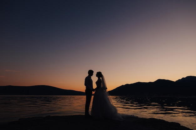 The bride and the groom standing on the pier near water and holding hands at the sunset