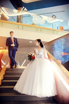Bride and groom standing on the stairs wedding