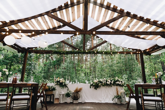 Bride and groom table decorated with flowers and lights in stylish boho wedding venue