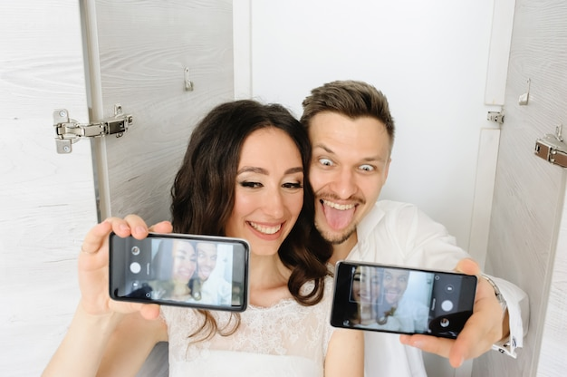 The bride and groom take a selfie in the closet.