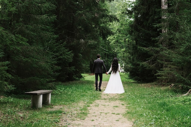 Bride and groom walk along the path of the park in the summer on the wedding day