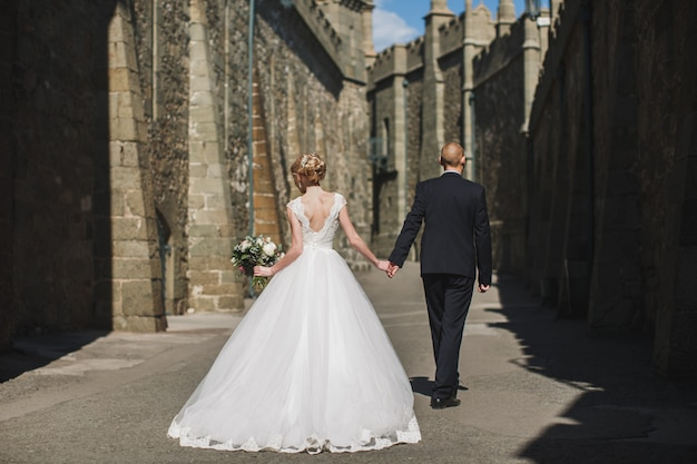 Bride and groom walk in the castle