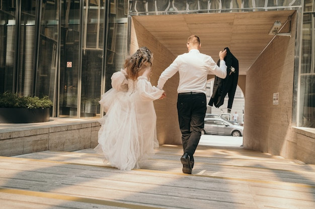 The bride and groom walk down the street by the hands. a stylish young couple walks