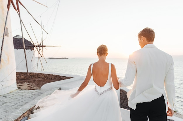 Bride and groom walk towards the sunset over the sea