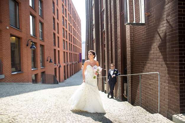 Bride and groom walking in the city, wedding day, marriage . bride and groom in urban . young couple in wedding day.