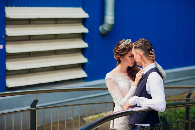 Bride and groom walking in the city, wedding day, marriage concept. bride and groom in urban background. young couple going on a stairs in wedding day.