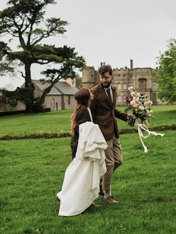 Bride and groom walking on a field overcast day, against the backdrop of an old castle