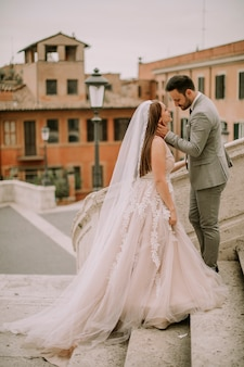 Bride and groom walking outdoors at spagna square and trinita' dei monti in rome, italy