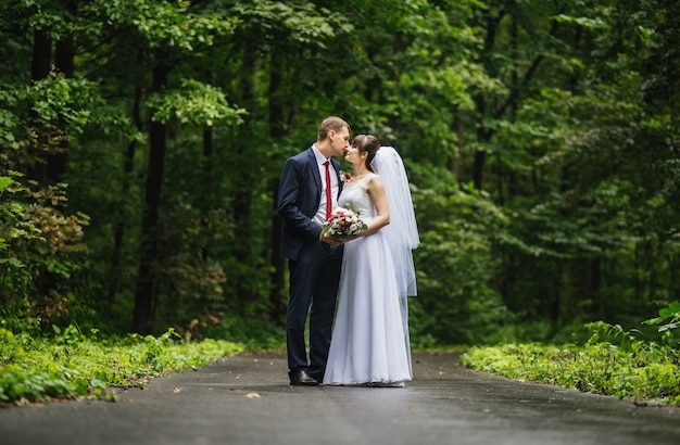 Bride and groom at wedding day, walking outdoor at summer on nature.
