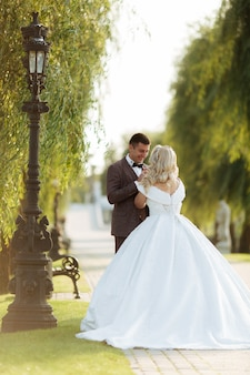 Bride and groom at wedding day walking outdoors on spring nature. bridal couple,