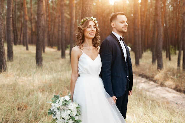 Bride and groom at wedding day walking outdoors on summer nature