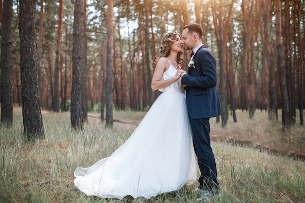 Bride and groom at wedding day walking outdoors on summer nature.