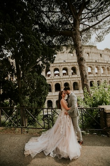 Bride and groom wedding posing in front of colosseum, rome, italy