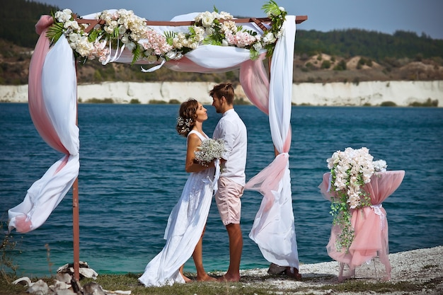 The bride and groom in white clothes with a bouquet of white flowers stand under an arch of flowers and fabric against the background of a blue lake and white sand