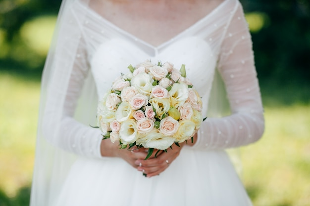 Bride and groom with a bouquet of red flowers and greens in hand