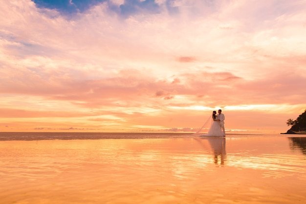Bride and groom with long veil on tropical beach at sunset wedding and honeymoon in the tropics
