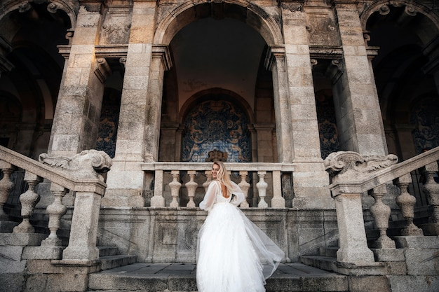 Bride in a half-turn stands on the stairs of the ancient building
